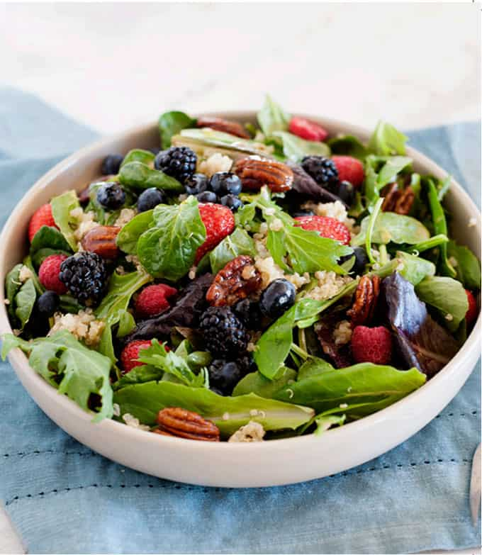 Green salad, in a white bowl, topped with mixed berries and toasted pecans.