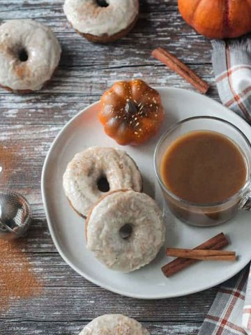 Two white frosted donuts on a plate with a glass mug of coffee and two cinnamon sticks.