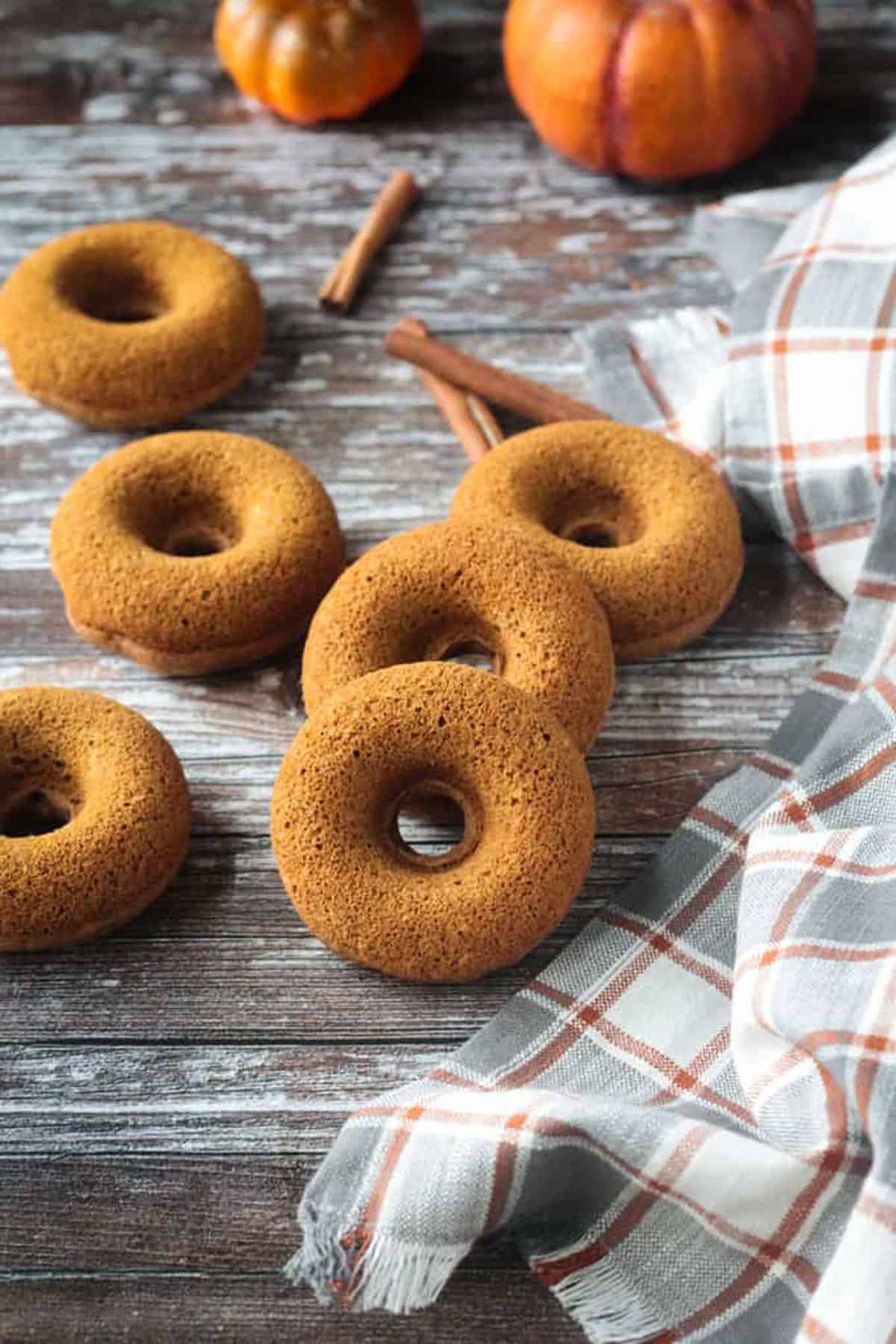 6 donuts lying sporadically on a wooden background.