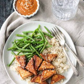 Dinner plate with tofu, green beans, and rice with a side of peanut sauce in a little bowl next to the plate.