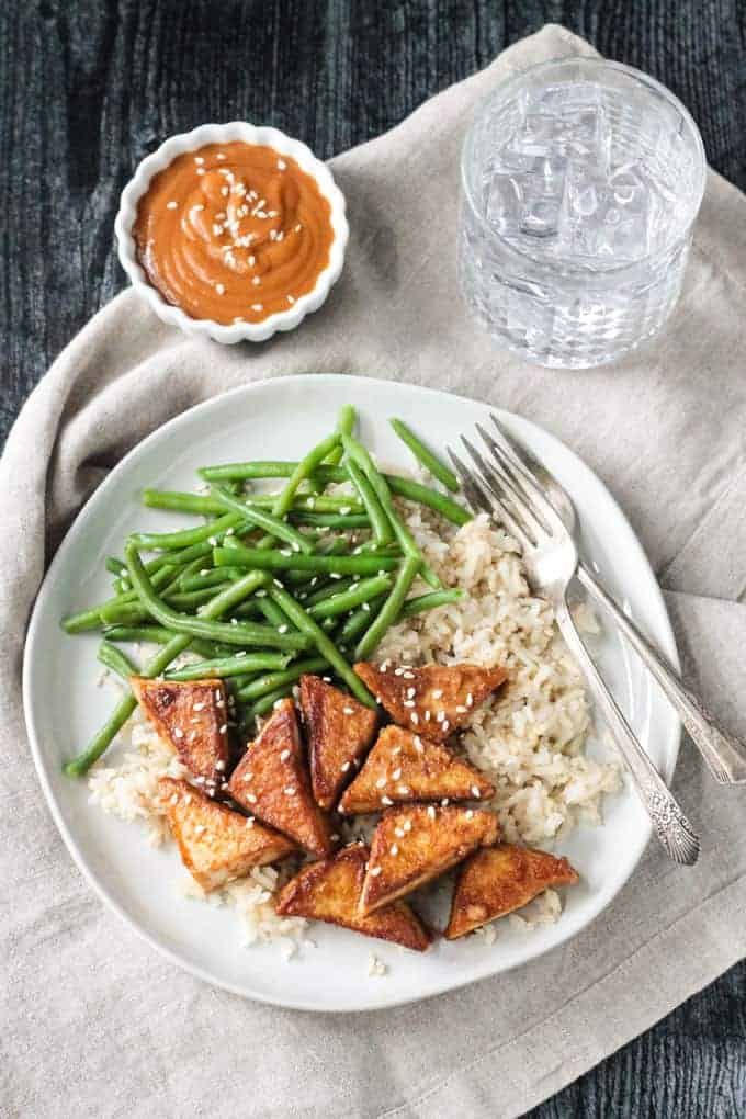 Dinner plate with pan fried tofu, green beans, and rice with a side of peanut sauce in a little bowl next to the plate.
