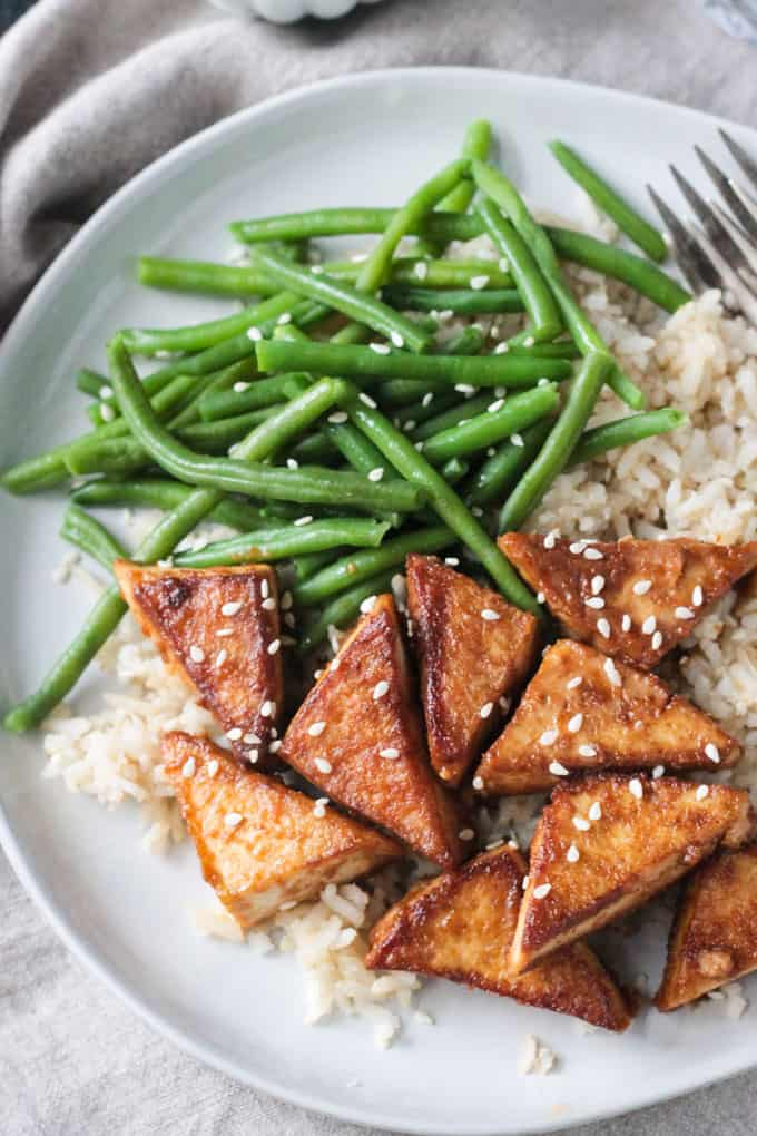 Pan fried tofu in peanut satay sauce sprinkled with sesame seeds