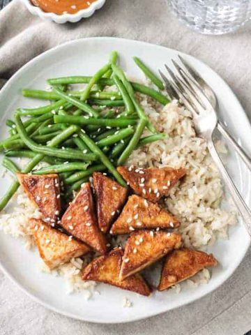 Pan friend tofu in peanut sauce plated with brown rice and green beans.