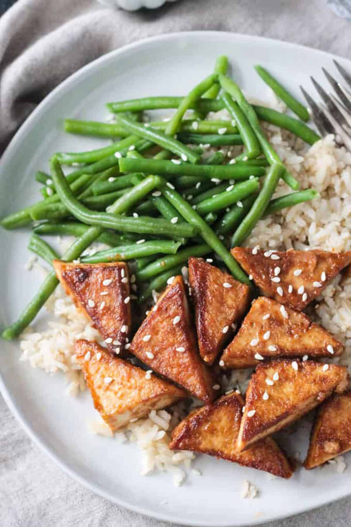 Close up of golden brown tofu triangles sprinkled with sesame seeds.
