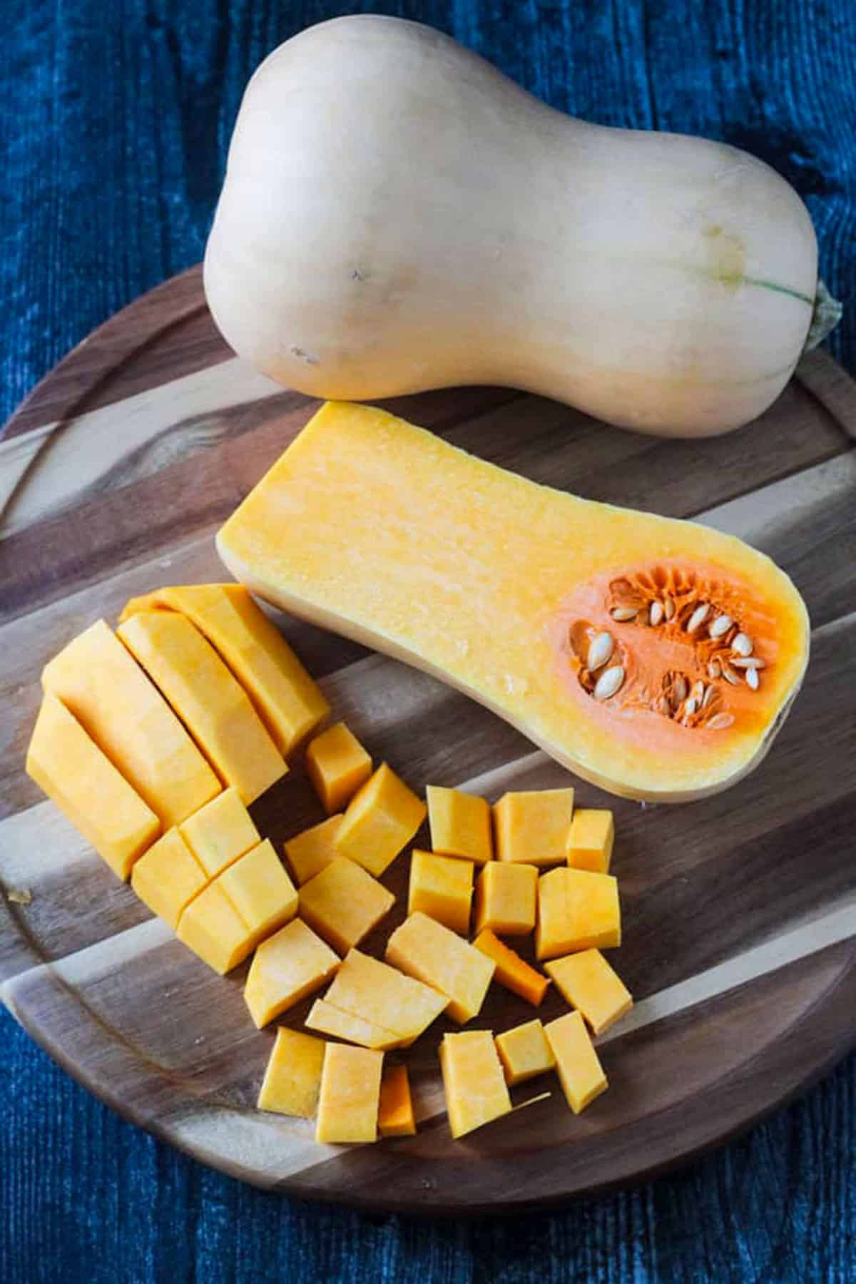 One whole butternut squash, one half butternut squash cut side up, and cubed pieces of butternut squash on a round wooden cutting board.