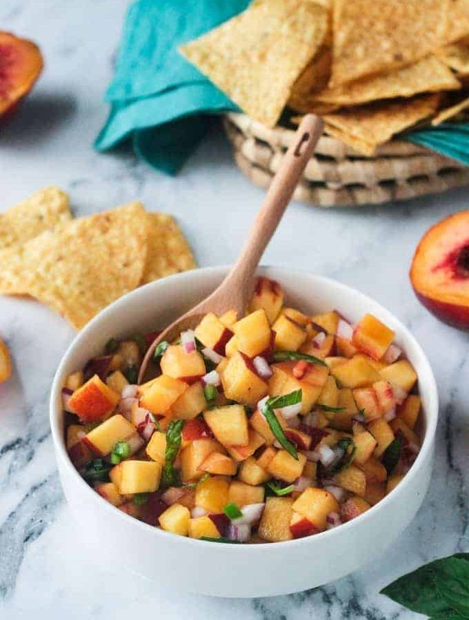 Flecks of chiffonade basil garnished on top of a fresh peach salsa recipe