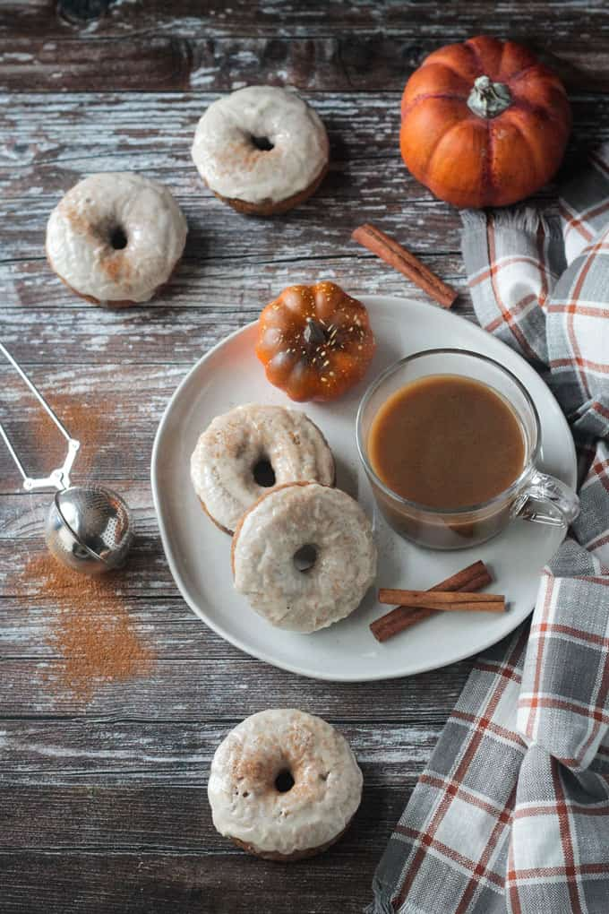Overhead view of a plate of 2 frosted pumpkin donuts with a side of coffee. Cinnamon shaker nearby with extra donuts scattered about the table.