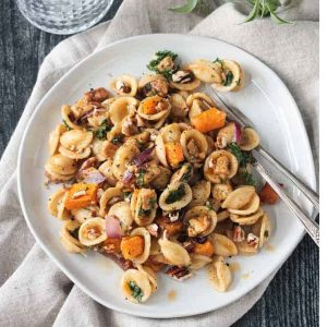 Fall Roasted Vegetable Pasta on a white plate with two forks.