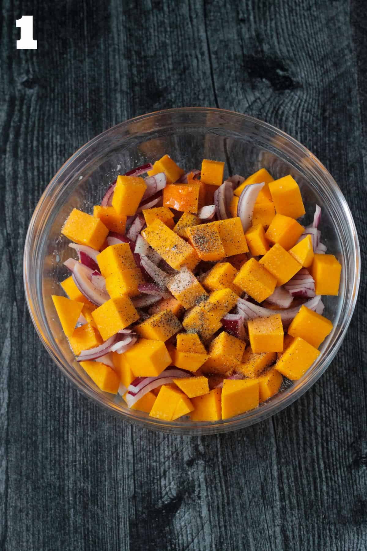 Raw chopped butternut squash and red onions with seasoning in a glass bowl.