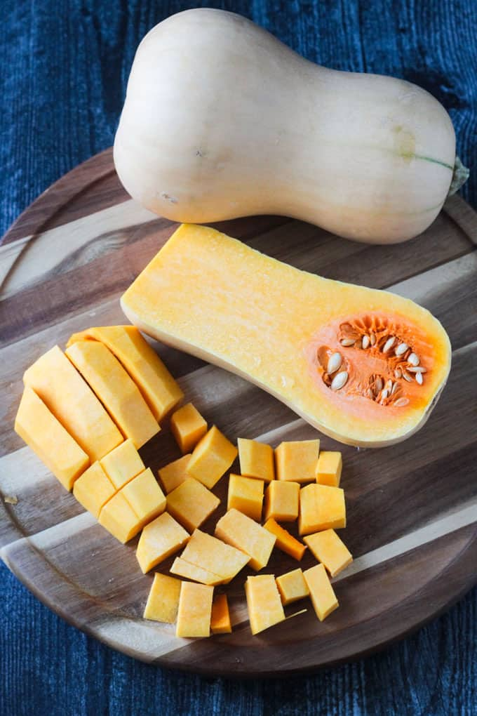 One whole butternut squash, one half butternut squash cut side up, and cubed pieces of butternut squash on a round wooden cutting board