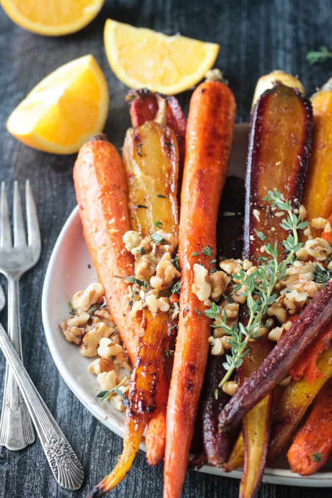 Close up of walnuts and thyme on top of the roasted carrots