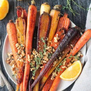 Plate of orange thyme rainbow roasted carrots topped with toasted walnuts .