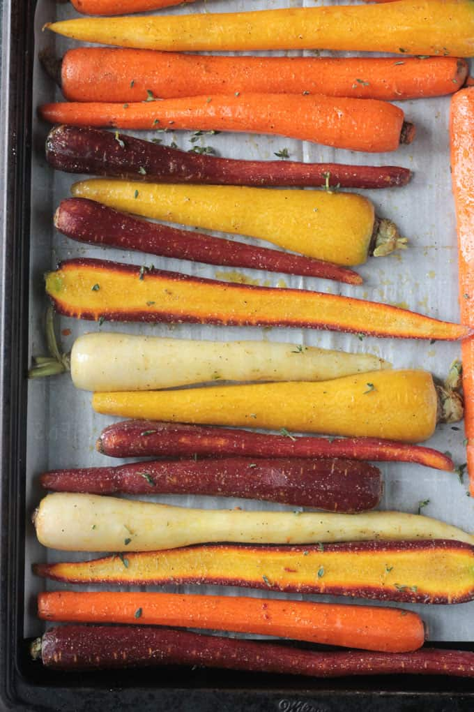 Carrots halved lengthwise and lined up on a baking sheet