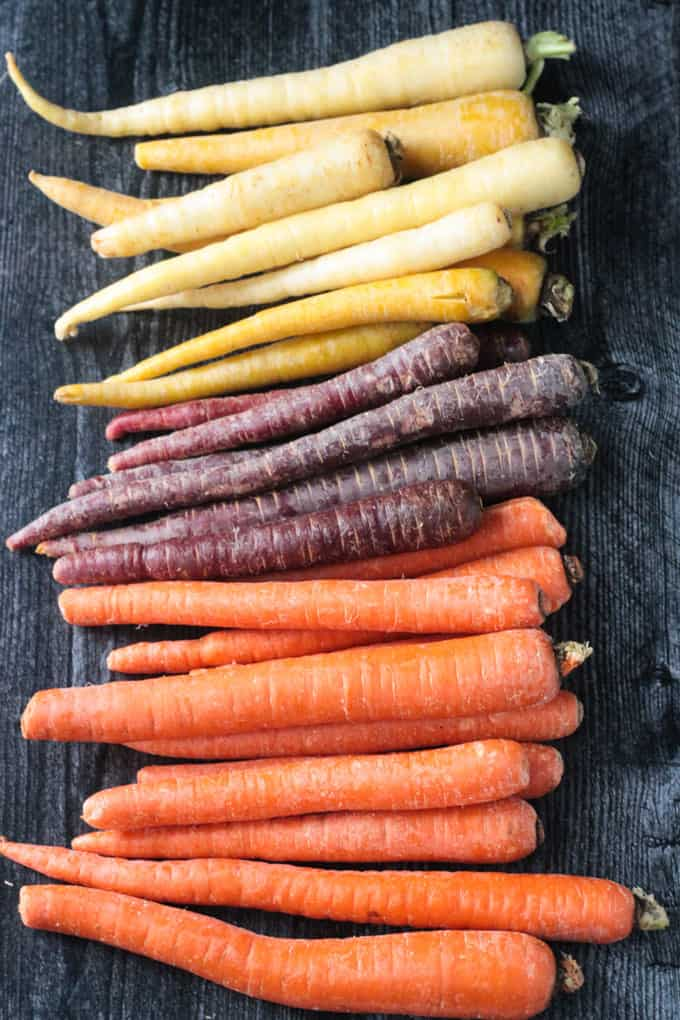 Yellow, purple, and orange carrots lined up in a rainbow