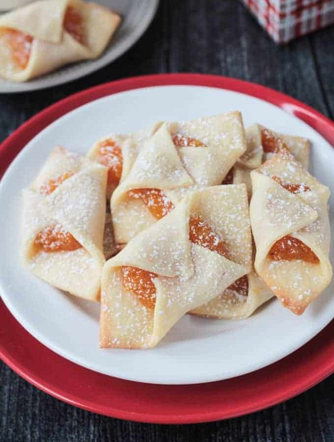 Close up view of a plate of kolaczki cookies filled with apricot jam and dusted with powdered sugar