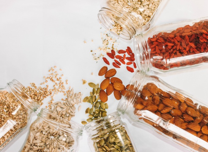 Assorted nuts and seeds spilling out of glass jars - part of a Plant based diet grocery list