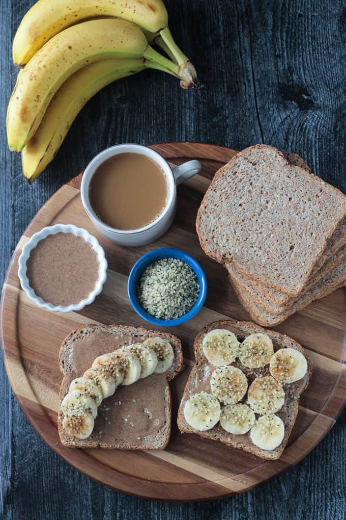 Bread, bananas, hemp seeds, coffee, and almond butter all laid out on a wooden platter.