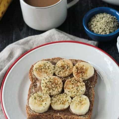 toast with fruit and nut butter next to a cup of coffee