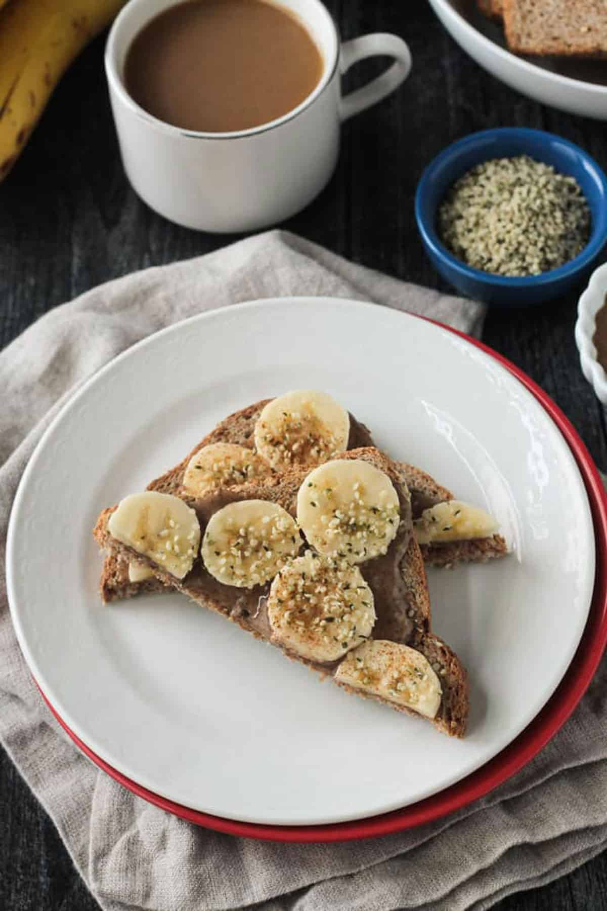 Bread cut in half diagonally and topped with almond butter, slices of bananas, and hemp seeds.