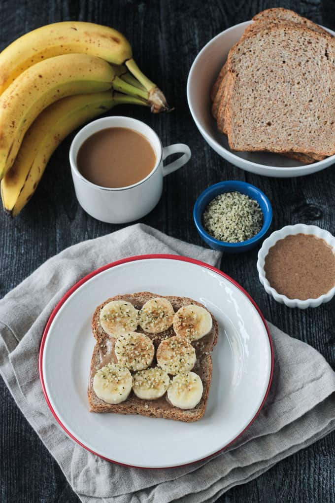 Breakfast toast on a white plate surrounded by a cup of coffee, bunch of bananas, small bowl of almond butter, and more toast slices.