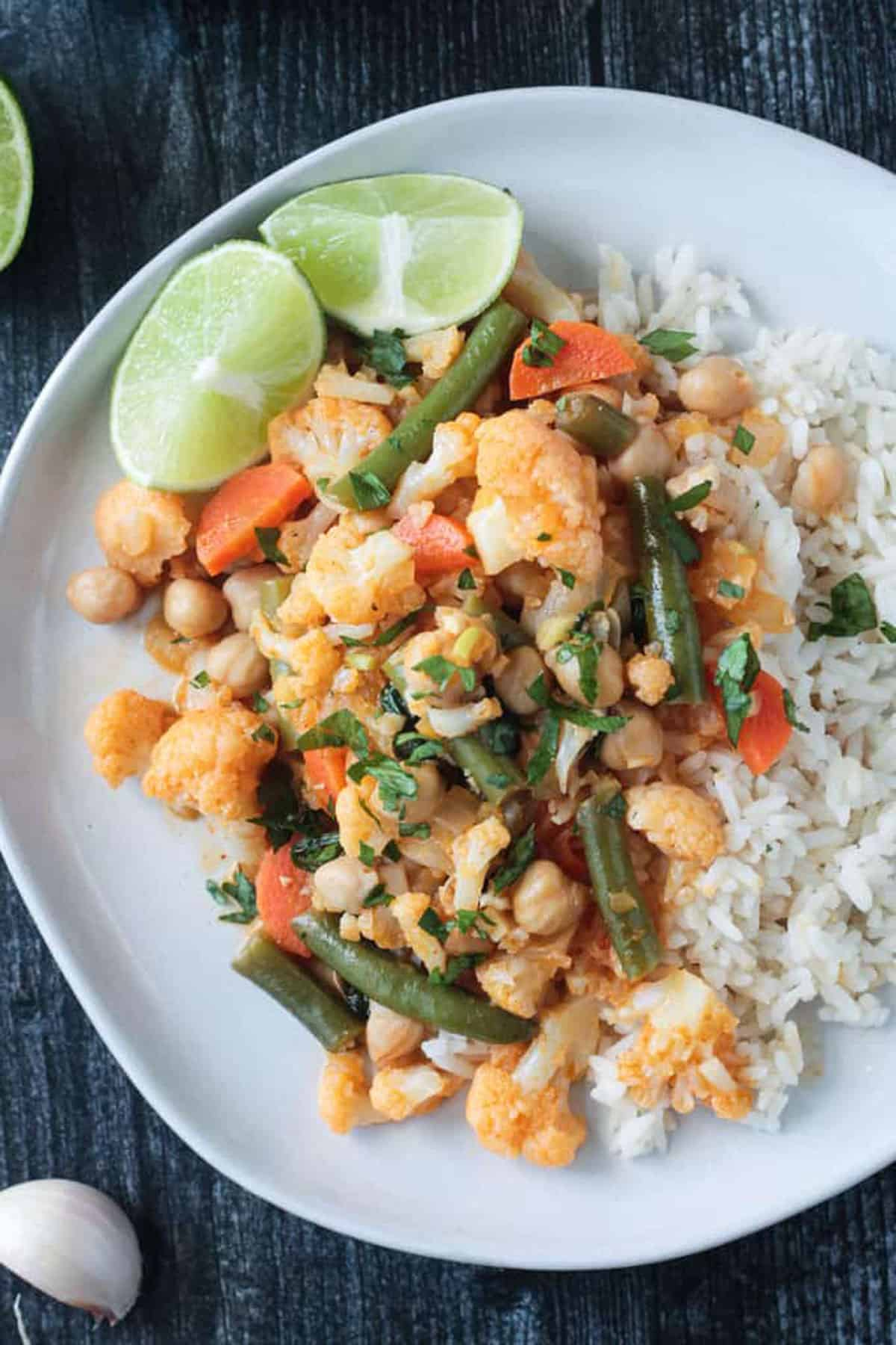 Close up of cauliflower, green beans and carrots in sauce next to rice.
