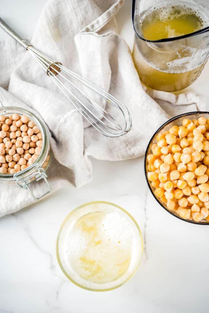 bowl of chickpeas next to a bowl of aquafaba