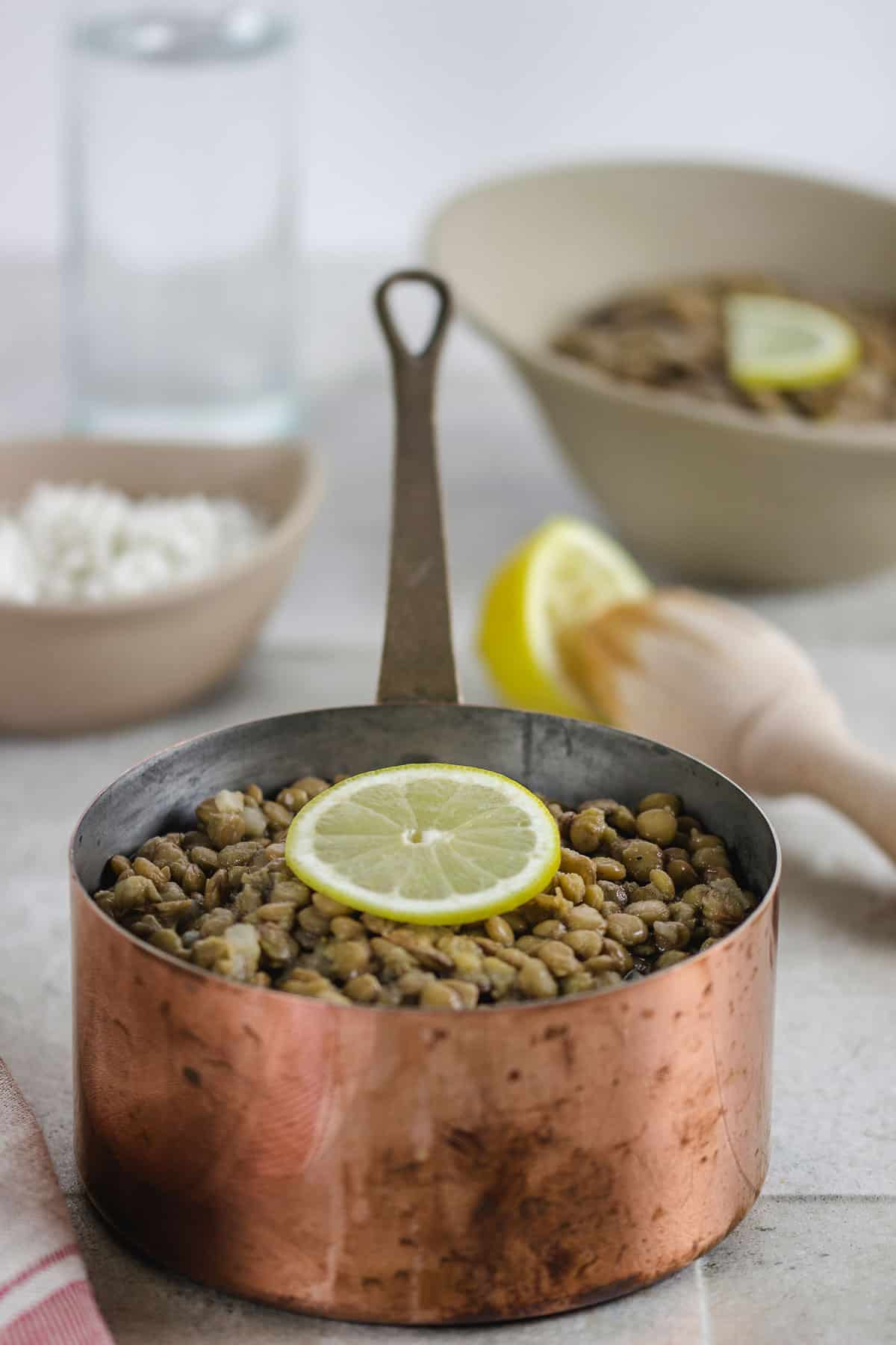 Brown lentils cooking in a copper pot with a lemon slice on top.