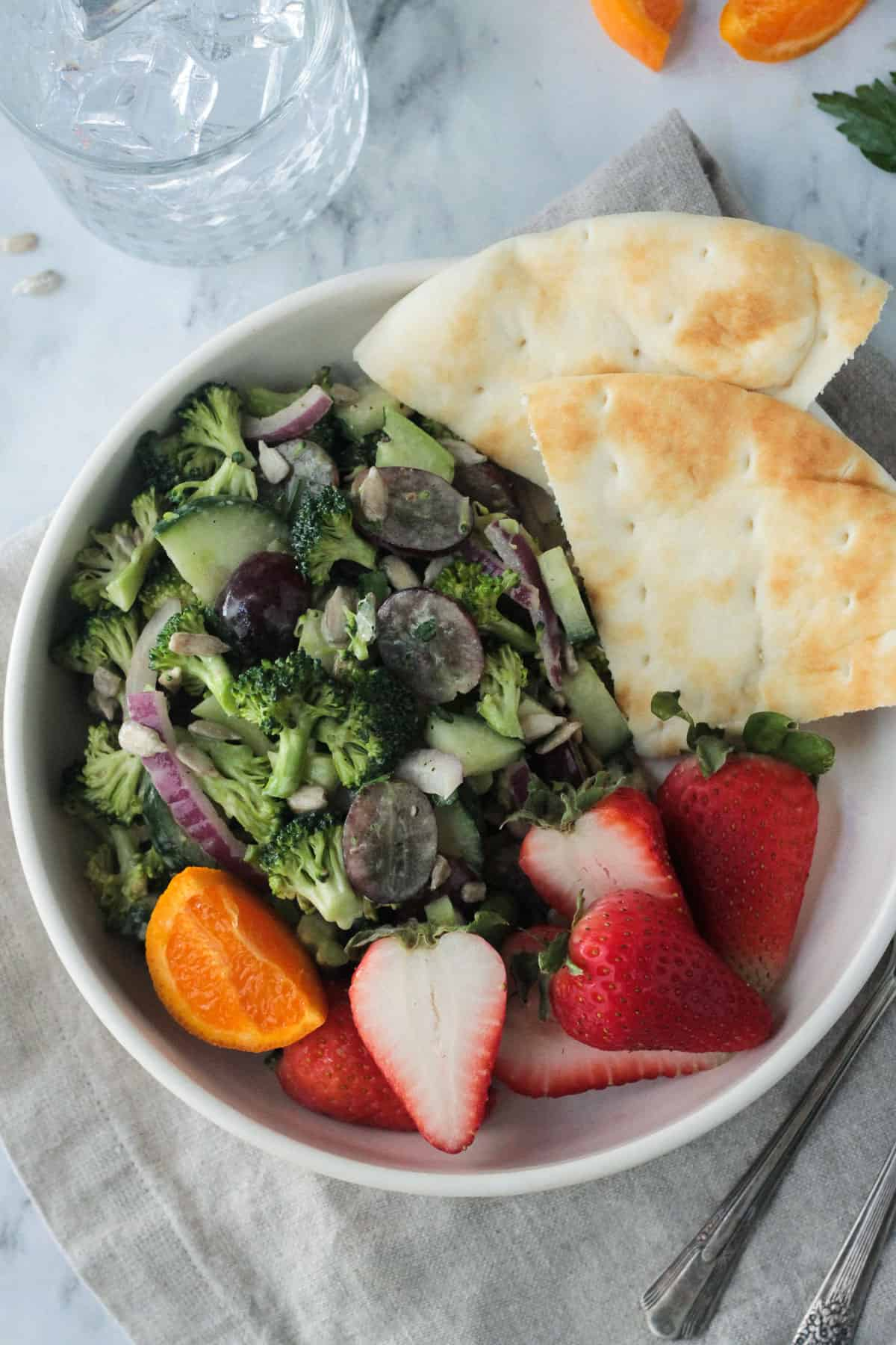 Broccoli salad in a white bowl with pita bread and fresh strawberries.