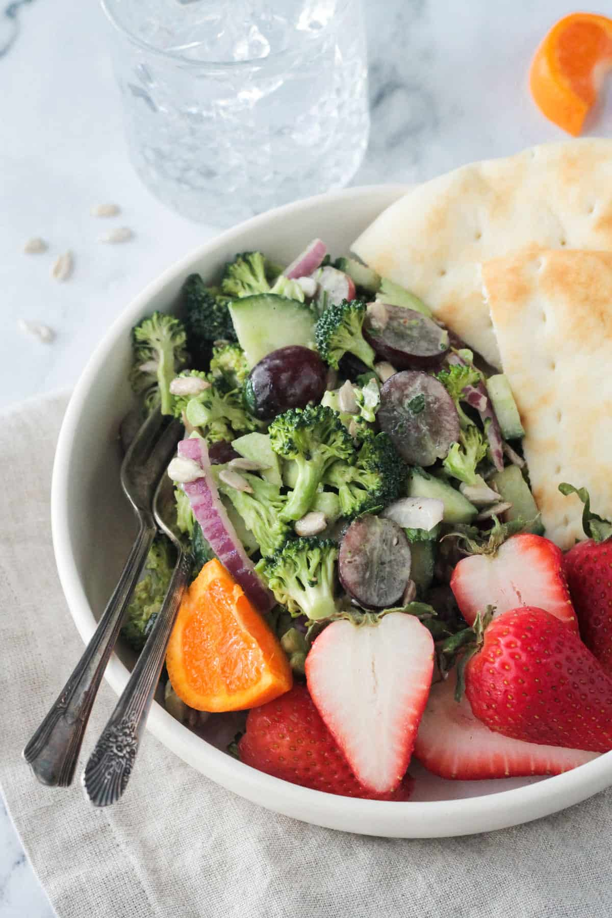 Two forks in a bowl of broccoli salad with grapes and red onion.