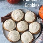 7 pumpkin cookies with white frosting on a plate.