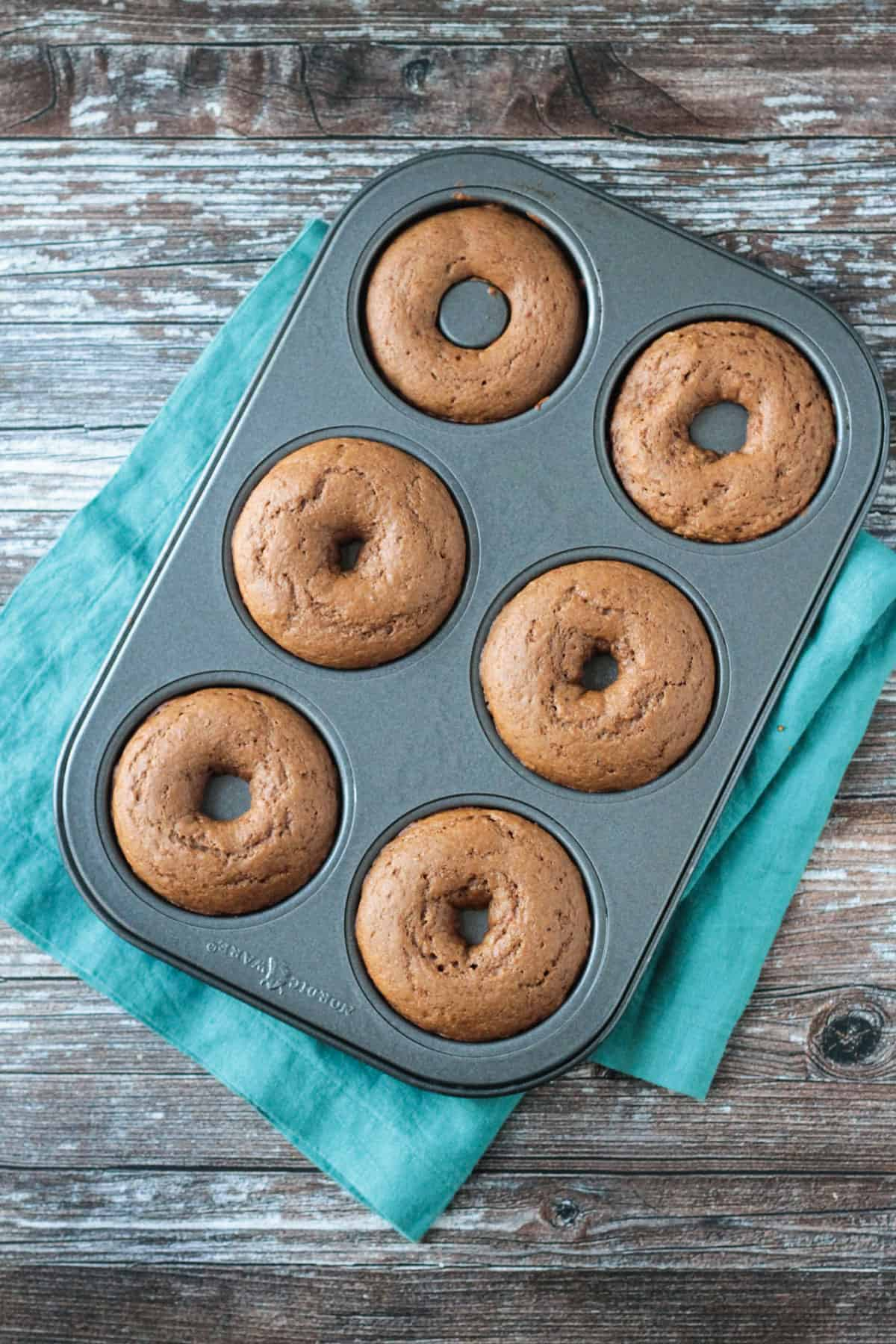 6 baked donuts in a donut pan.