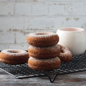 Stack of three cider donuts on a black wire cooling rack in front of a coffee mug.