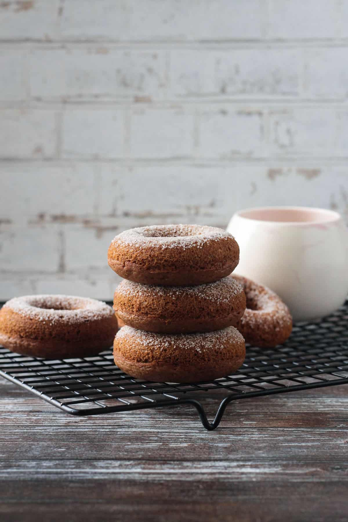 Stack of three cider donuts on a black cooling rack in front of a mug.