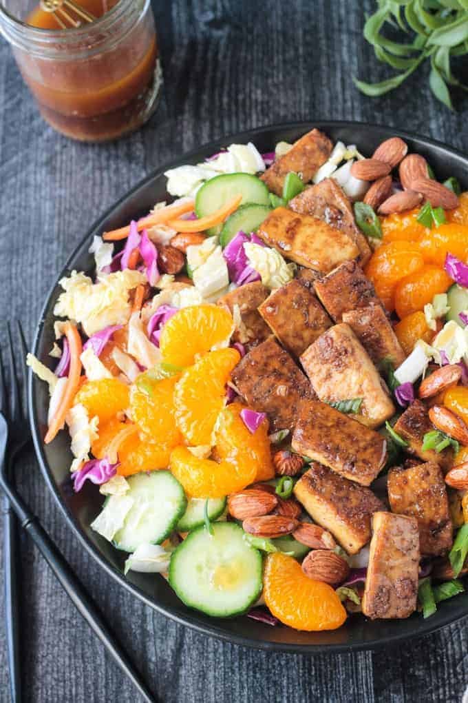 close up of the mandarin oranges and baked tofu on top of this recipe in a bowl