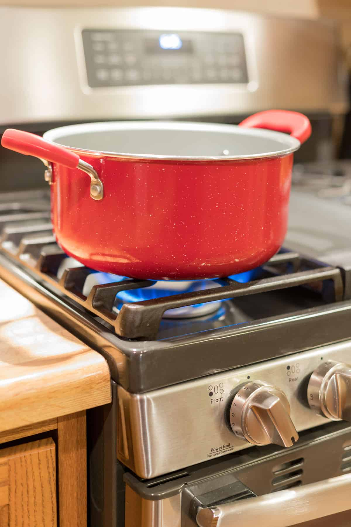 Red enamel pot over a flame on a gas range stove.