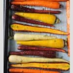 Roasted rainbow carrots on a parchment lined baking sheet.