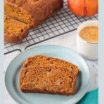Two slices of pumpkin bread on a blue plate in front of a loaf and cup of coffee.