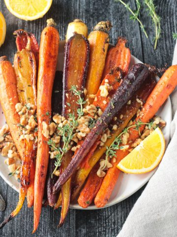 Plate of roasted rainbow carrots topped with walnuts and thyme leaves.