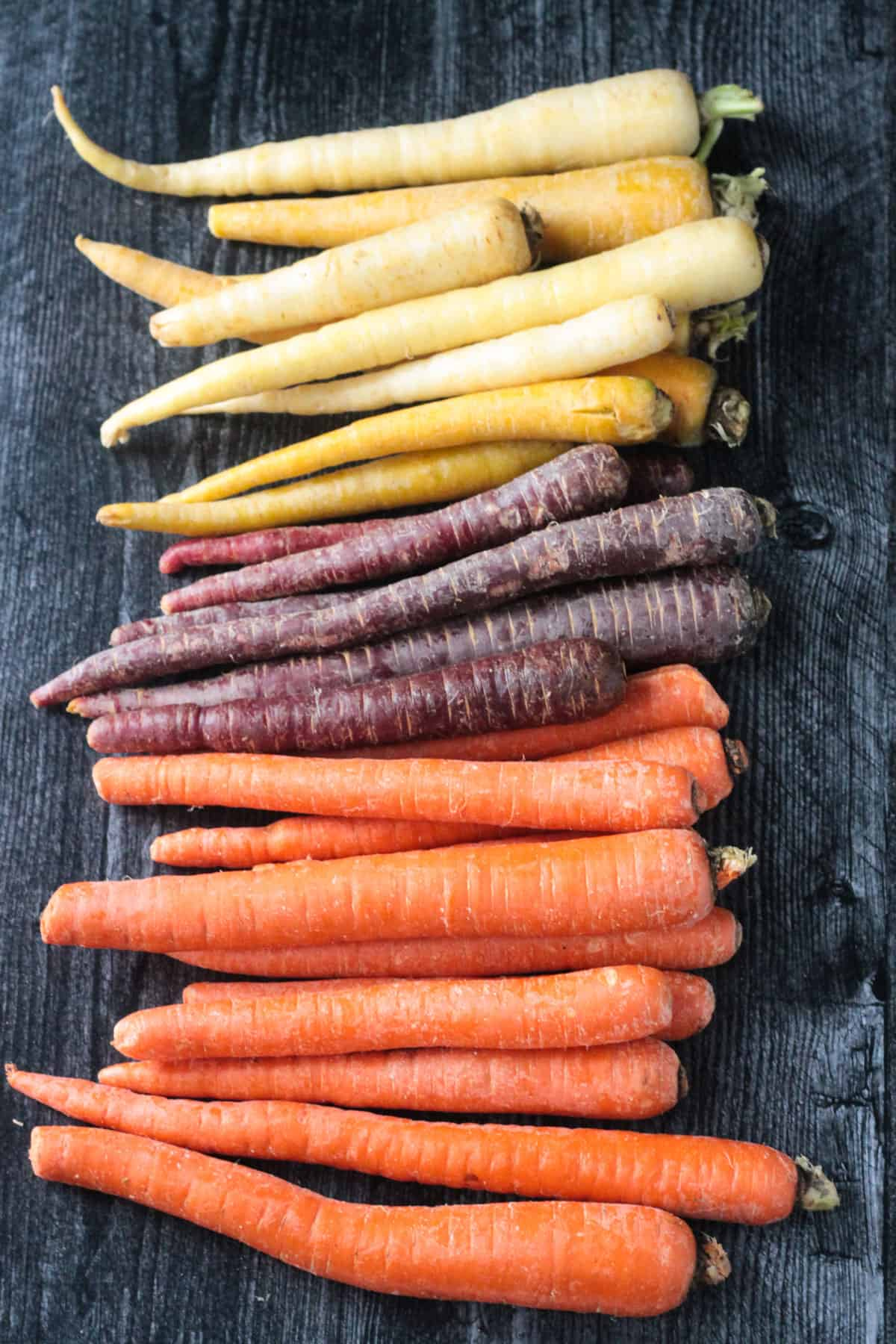 A variety of different colored carrots lined up in a row.