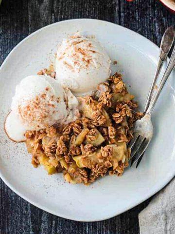 Vegan apple crisp with two scoops of vanilla cream and sprinkle of cinnamon.