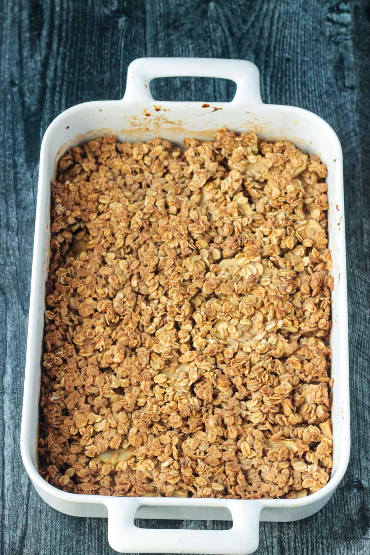 Finished dish - baking pan of baked vegan apple crisp.