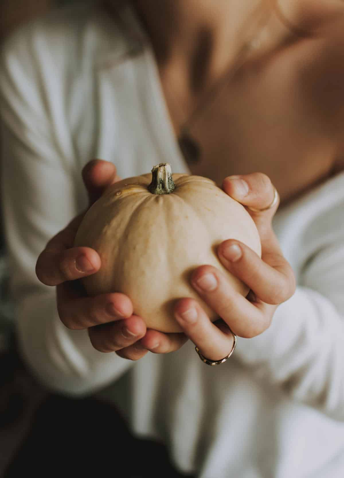 Woman in white sweater holding  a small white pumpkin.