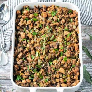 Finished dish of vegan stuffing with mushrooms in a white baking dish.