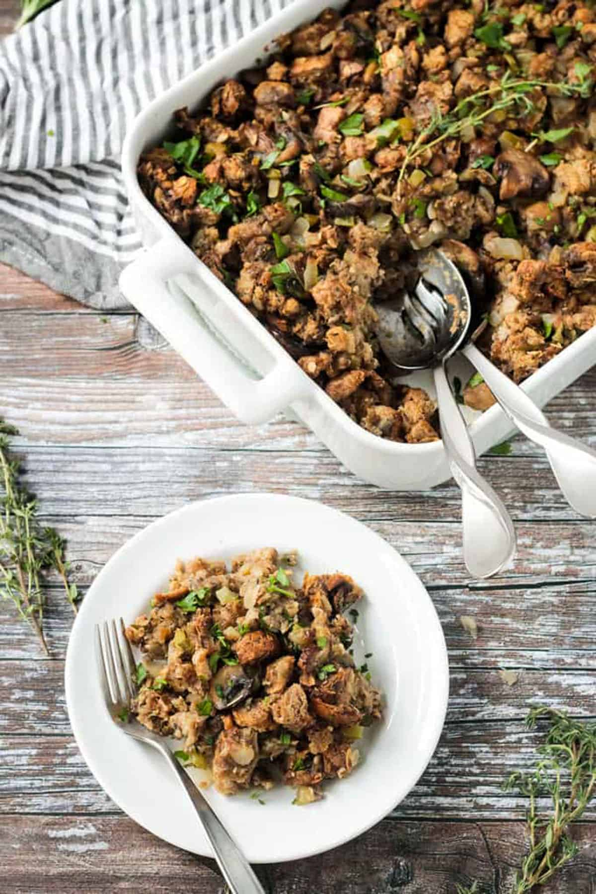 Serving of stuffing on a white plate in front of the baking dish.