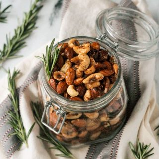 Open jar of spiced roasted nuts surrounded by fresh rosemary sprigs.