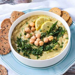 Hummus recipe without tahini garnished with chopped parsley and two lemon slices.