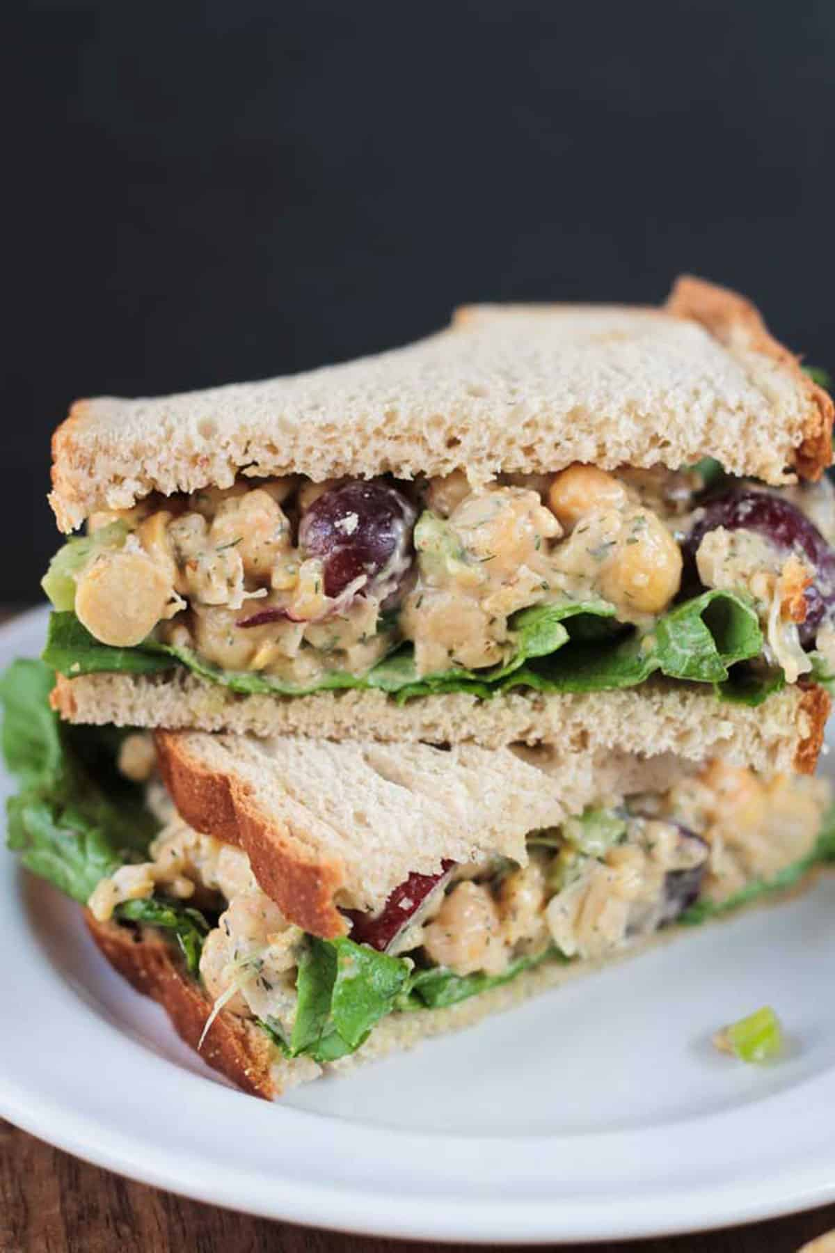 Two sandwich halves filled with vegan chickpea salad stacked on each other.