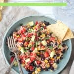 Rice, black beans, corn, diced red peppers, and avocado mixed together on a blue plate with a fork.