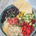 Two tortilla chips on the side of beans and rice topped with avocado and salsa.