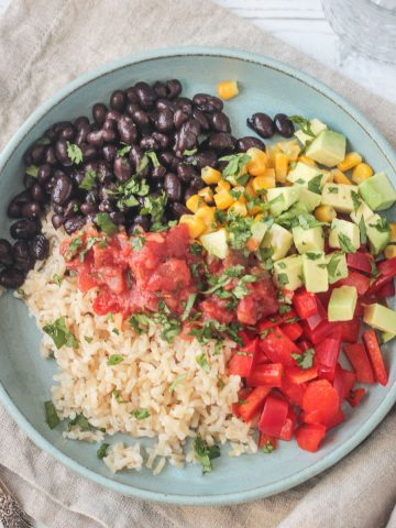 Vegan burrito bowl with rice, beans, corn, peppers, salsa, and avocado on a plate.